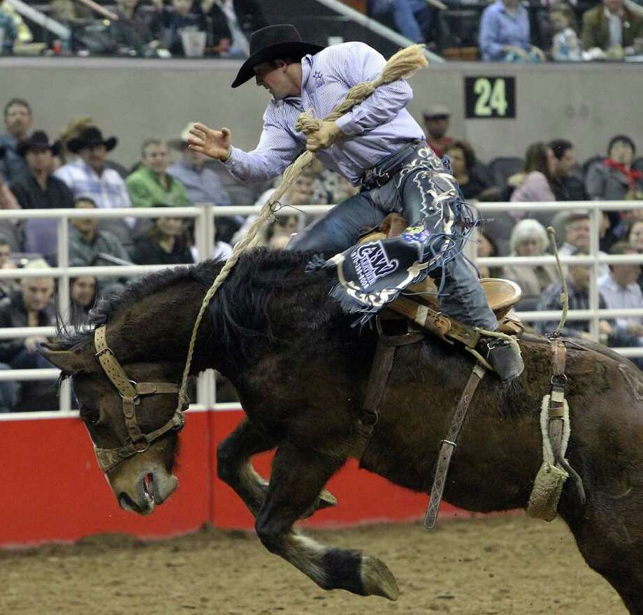 Cody Angland attempts to ride Alley Cone during the Saddle Bronc Riding competition at the 2012 San Antonio Stock Show & Rodeo on Friday, Feb. 24, 2012. Kin Man Hui/San Antonio Express-News Photo: Kin Man Hui, SAN ANTONIO EXPRESS-NEWS / ©2012 SAN ANTONIO EXPRESS-NEWS