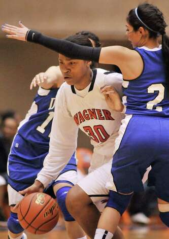 Wagner's Tesha Smith (center) drives around Del Rio's Valeria Guevara during the first half of their playoff game on Friday, Feb. 24, 2012, at UTSA. Wagner won 58-46. Photo: Darren Abate, For The Express-News