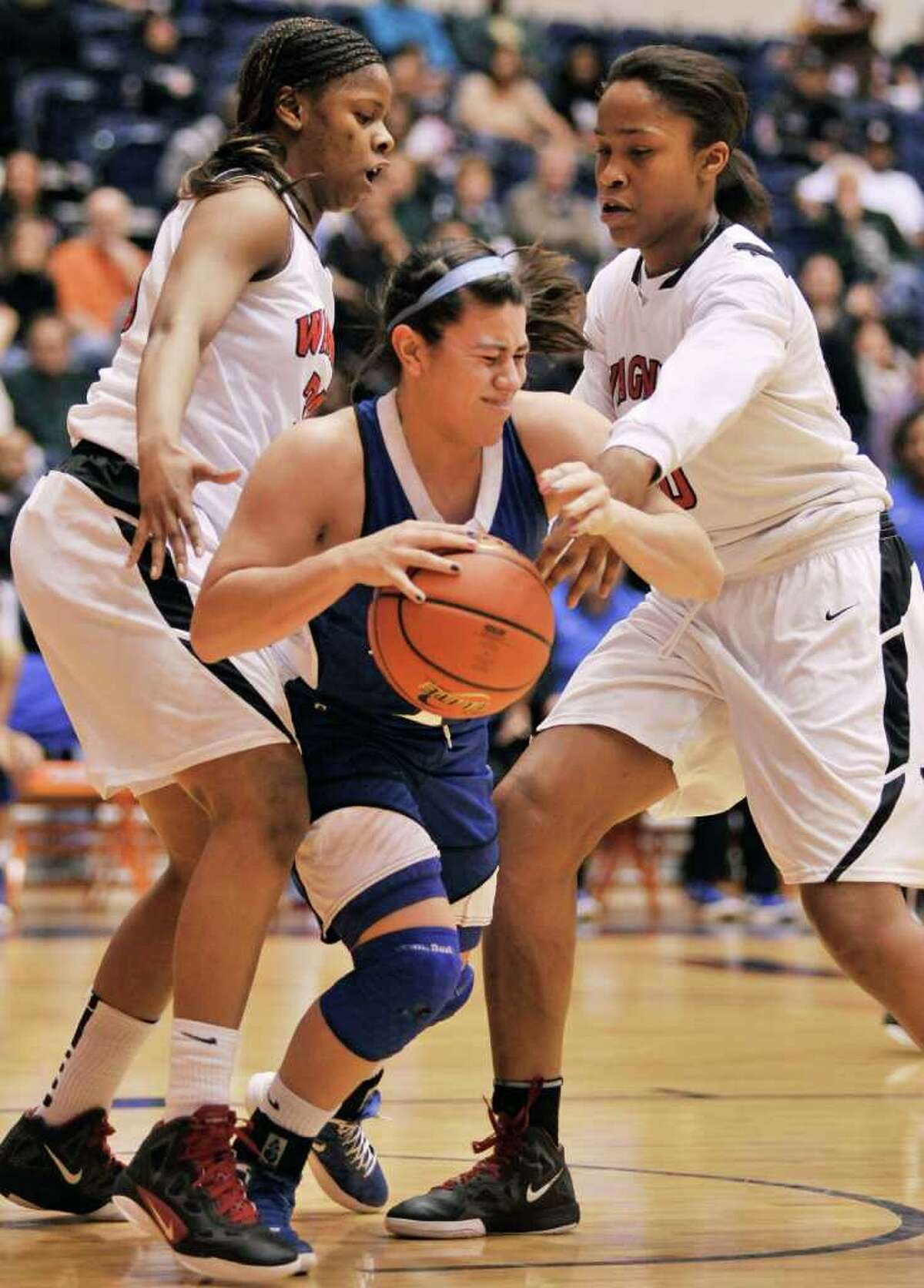 Wagner's Kaelynn Wilson (left) and Tesha Smith (right) try to strip the ball from Del Rio's Avianna Glavan during the first half their playoff game on Friday, Feb. 24, 2012, at UTSA. Wagner won 58-46.