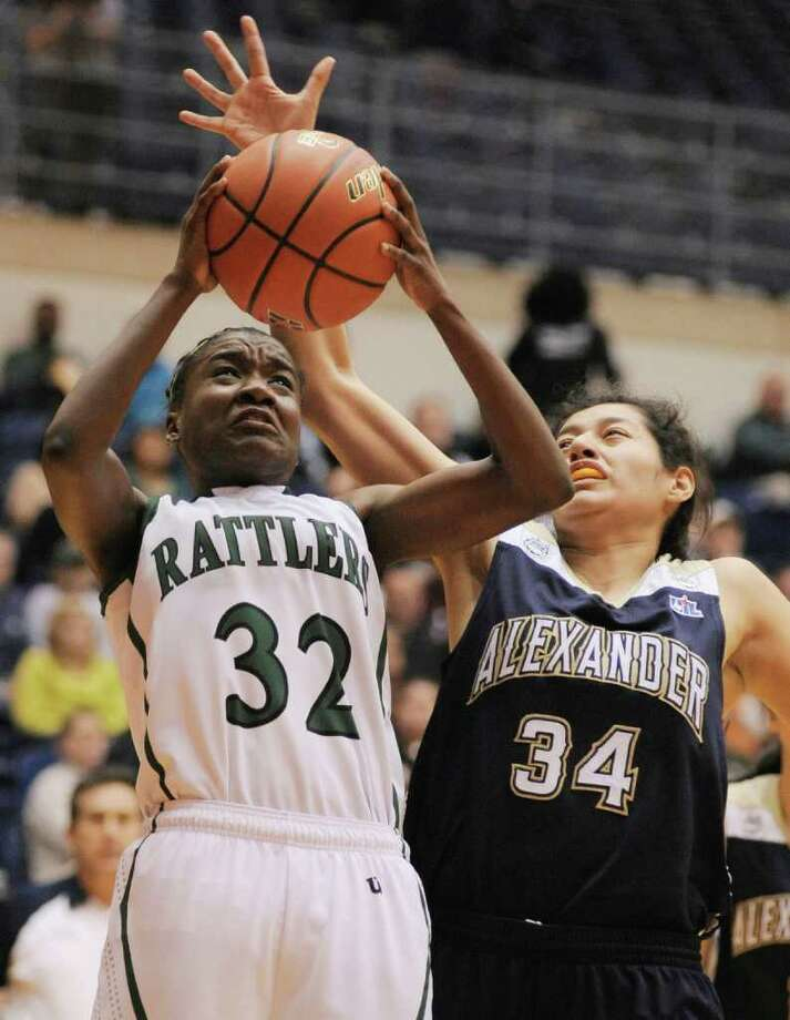 Reagan's Moriah Mack (left) fights Laredo Alexander's Lluvia Murillo for a rebound during the first half of their playoff game on Friday, Feb. 24, 2012, at UTSA. Reagan beat Laredo Alexander 44-38. Photo: Darren Abate, For The Express-News