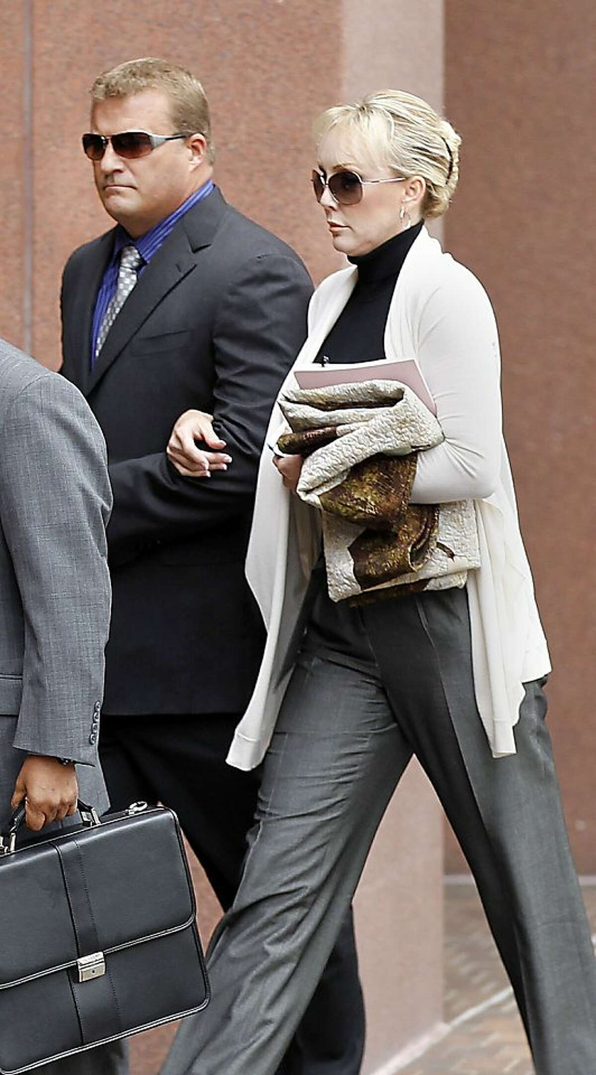Defendant Theresa Erickson, right, and her husband John Erickson, arrive at Federal Court in downtown San Diego, Friday Feb. 24, 2012. Erickson, 44, a California lawyer who was a respected reproductive law specialist was sentenced Friday to five months in prison and nine months of home confinement for her role in what prosecutors say was a baby-selling scheme. U.S. District Court Judge Anthony Bataglia also ordered Theresa Erickson, 44, to pay a $70,000 fine. Co-defendant Carla Chambers was sentenced to five months in prison and seven months in home confinement. Both women had faced up to five years in prison. (AP Photo/U-T San Diego, ) SAN DIEGO COUNTY OUT; NO SALES; COMMERCIAL INTERNET OUT; FOREIGN OUT