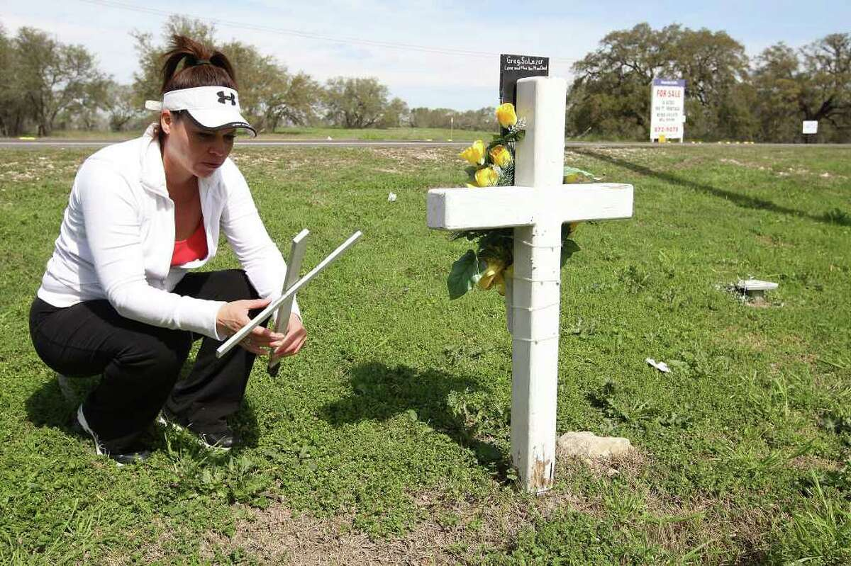 METRO -- Margot Salazar, 44, holds one of the crosses at a roadside memorial for her husband, Greg Salazar at the corner of Potranco Road and American Lotus, Thursday, Feb. 23, 2012. On the center right, is a base that used to hold a Texas Department of Transportation sign in memory of her husband. On March 2008, Salazar was riding his motorcycle by that intersection when struck by a hit-and-run driver. Jose Luis Morales was later convicted of intoxication manslaughter. The memorial was purchases by the victim's parent through a TxDOT program. Jerry Lara/San Antonio Express-News