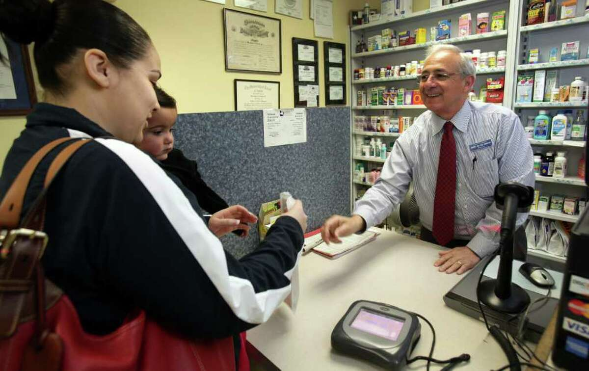 Mario de los Santos, right, owner of Mario's Pharmacy, fills prescriptions for customer Reyna Rios and her 1 yr old daughter Samantha Rios. De los Santos' business will be affected when the state switches its Medicaid drug benefit from fee-for-service to managed care. Friday, Feb. 24, 2012.