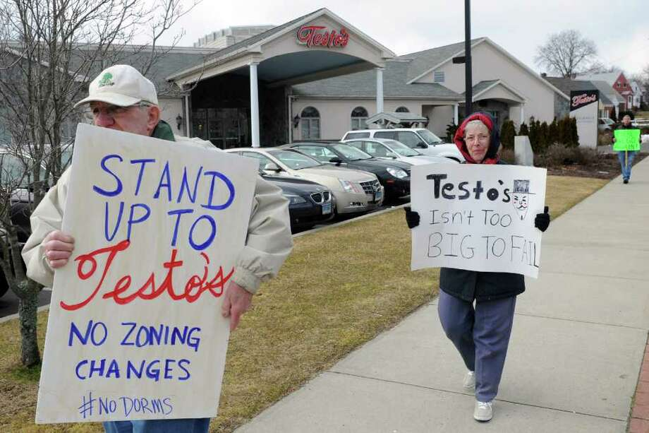 William and Ester Becker, of Bridgeport, protest in front of Testo's Restaurant, on Madison Ave. in Bridgeport, Conn. Saturday, Feb. 25th, 2012. Mario Testa, the restaurant's owner and Democratic Town Committee Chair will be asking a zoning board Monday for approval to change the land his restaurant sits on from a residential zone to an office/retail zone. Photo: Ned Gerard / Connecticut Post