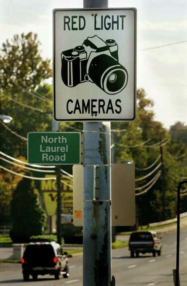 Cars drive past a red light camera sign on Route 1 October 18, 2002 in Laurel, Maryland. Connecticut legislators are considering enabling municipalities to use the cameras, but there is conflicting evidence on whether they actually improve safety. (Photo by Mario Tama/Getty Images) Photo: Mario Tama, Getty Images / 2002 Getty Images