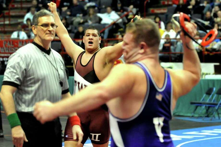 Ravena's Alex Soutiere, center, celebrates his upset win as opponent Holley's Kacee Sauer, right, throws his headset after their Division II 285-pound semi-final match during the State Wrestling Tournament on Saturday, Feb. 25, 2012, at Times Union Center in Albany, N.Y. (Cindy Schultz / Times Union) Photo: Cindy Schultz / 00016194A