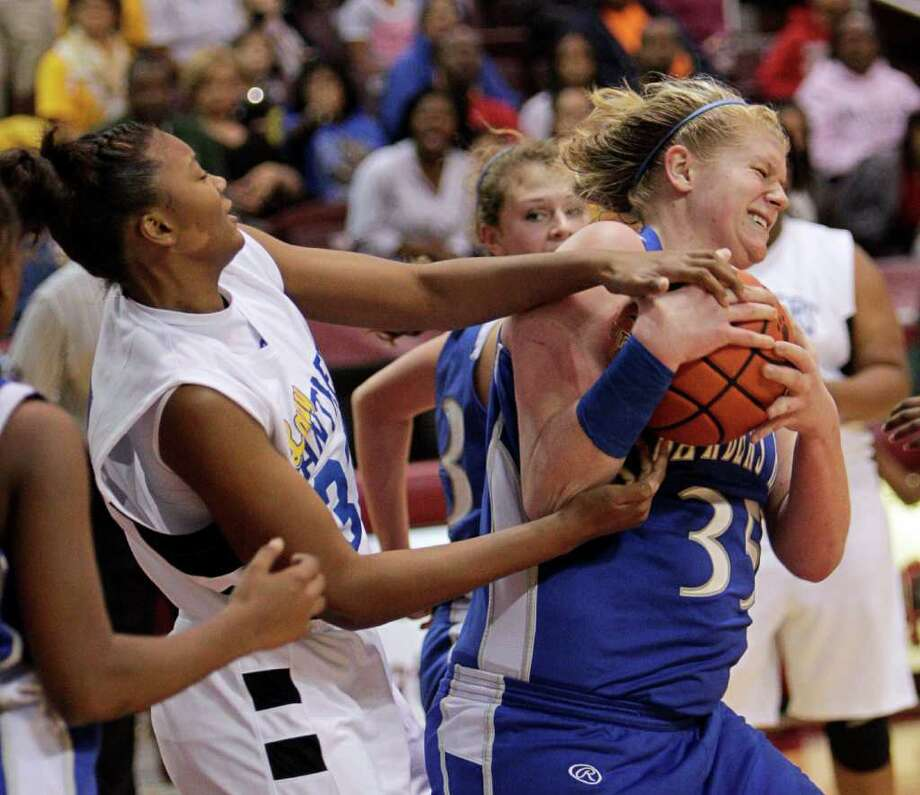 Barbers Hill's Kendall Shaw #35 rips the ball away from Beaumont Ozen's Jerica Bolin #33 during the Region III 4A girls basketball finals between Barbers Hill and Beaumont Ozen at the M.O. Campbell Center Feb.  25, 2012 in Houston, Tx. Photo: Bob Levey, Houston Chronicle / ©2012 Bob Levey