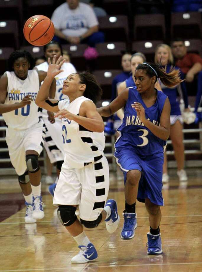 Beaumont Ozen's Asia Booker #12 attempts to get possession of the ball as she is pressured by Barbers Hill's Kimi Carter #3 during the Region III 4A girls basketball finals between Barbers Hill and Beaumont Ozen at the M.O. Campbell Center Feb.  25, 2012 in Houston, Tx. Photo: Bob Levey, Houston Chronicle / ©2012 Bob Levey