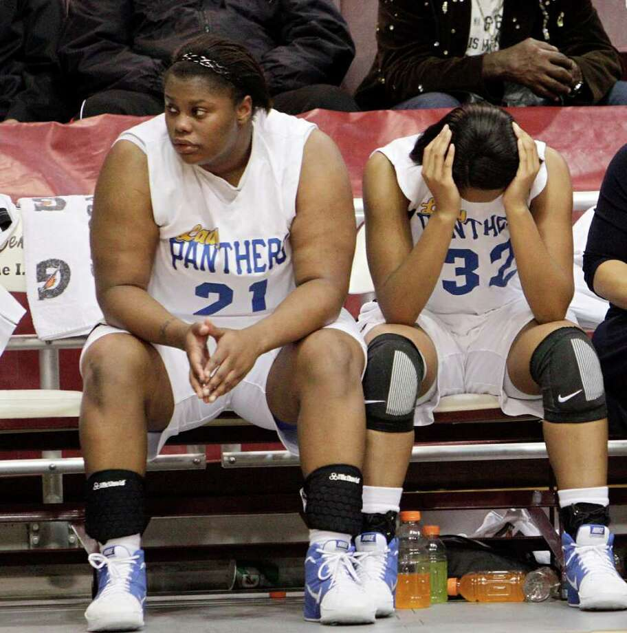 Beaumont Ozen's Nekia Jones #21 and Alexandra Moten #32 sit dejected on the bench after losing during the Region III 4A girls basketball finals between Barbers Hill and Beaumont Ozen at the M.O. Campbell Center Feb.  25, 2012 in Houston, Tx. Photo: Bob Levey, Houston Chronicle / ©2012 Bob Levey