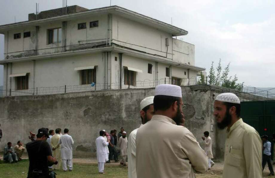 Residents of Abbottabad, Pakistan, stand in May 2011 near where Osama bin Laden was killed. The Navy SEAL who shot bin Laden said he encountered him on the third floor, just inside a doorway, with his hands on a woman's shoulders, pushing her forward. Photo: AP