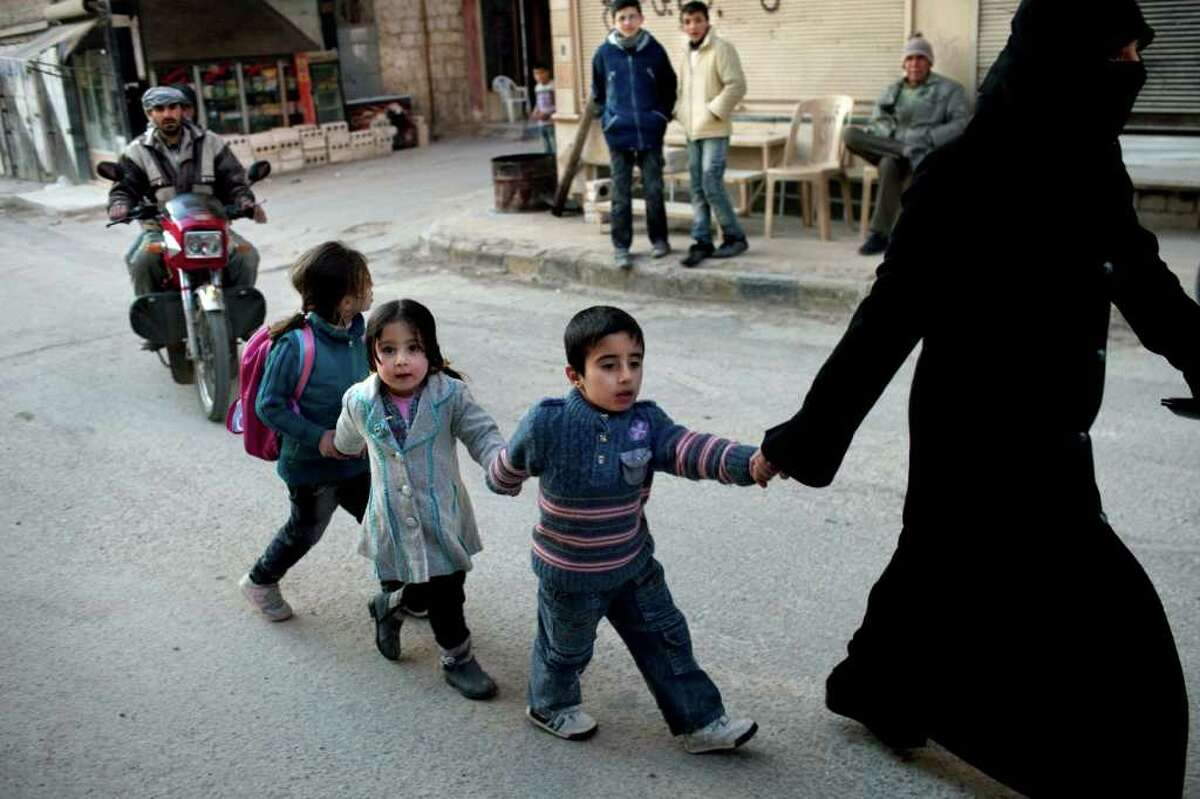 A woman walks with children in Kafar Taharim, north Syria, Saturday, Feb. 25, 2012. The town of Kafar Taharim is under control of the Free Syrian Army for the past month, and people continue a normal life due to the lack of combat with government military forces.