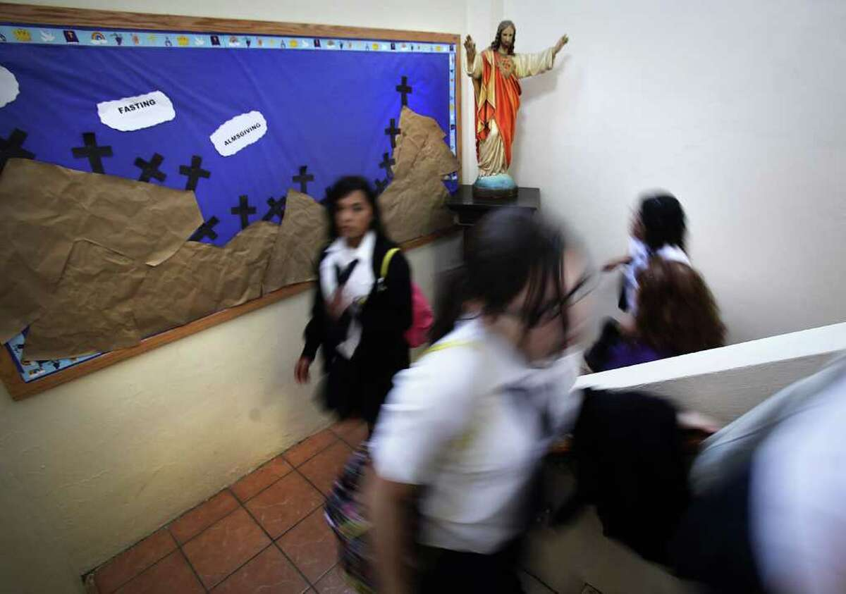 Students hurry past a religious statue in a stairwell at St. Leo the Great Catholic School. Students and faculty at the school will see an increase in the student body as The Archdiocese of San Antonio announced the closing of St. Cecilia and St. Philip of Jesus schools. Friday, Feb. 24, 2012.