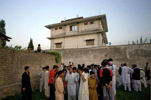 FILE - In this May 3, 2011 file photo, local residents gather outside a house, where al-Qaida leader Osama bin Laden was caught and killed in Abbottabad, Pakistan.  Local residents say Pakistan has started to demolish the compound in the northwest city of Abbottabad where Osama bin Laden lived for years and was killed by U.S. commandos. Two residents say the government brought in three mechanized backhoes Saturday, Feb. 25, 2012,  and began destroying the tall outer walls of the compound after sunset. They set up floodlights to carry out the work.    (AP Photo/B.K.Bangash,File) Photo: Anjum Naveed