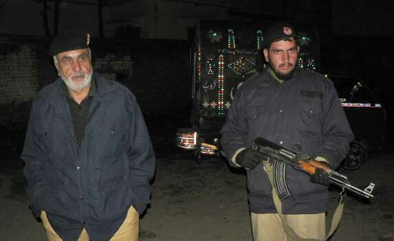 Pakistani police officers stand guard in the vicinity of the compound of Osama bin Laden in Abbottatabd, Pakistan on Saturday, Feb 25, 2012. Local residents say Pakistan has started to demolish the compound in the northwest city of Abbottabad where Osama bin Laden lived for years and was killed by U.S. commandos. Two residents say the government brought in three mechanized backhoes Saturday, Feb. 25, 2012, and began destroying the tall outer walls of the compound after sunset. They set up floodlights to carry out the work. (AP Photo/Aqeel Ahmed) Photo: Aqeel Ahmed / AP