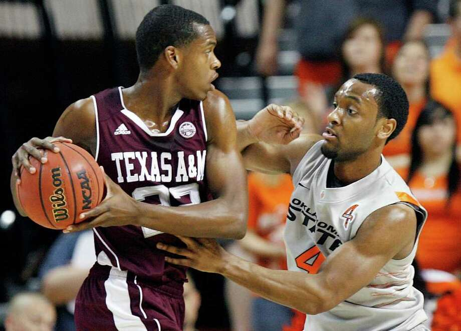 Texas A&M's Khris Middleton, left, holds the ball as Oklahoma State's Brian Williams defends during an NCAA college basketball game in Stillwater, Okla., Saturday, Feb. 25, 2012. Oklahoma State won, 60-42. (AP Photo/The Oklahoman, Nate Billings) TABLOIDS OUT Photo: Nate Billings, Associated Press / NATE BILLINGS/THE OKLAHOMAN