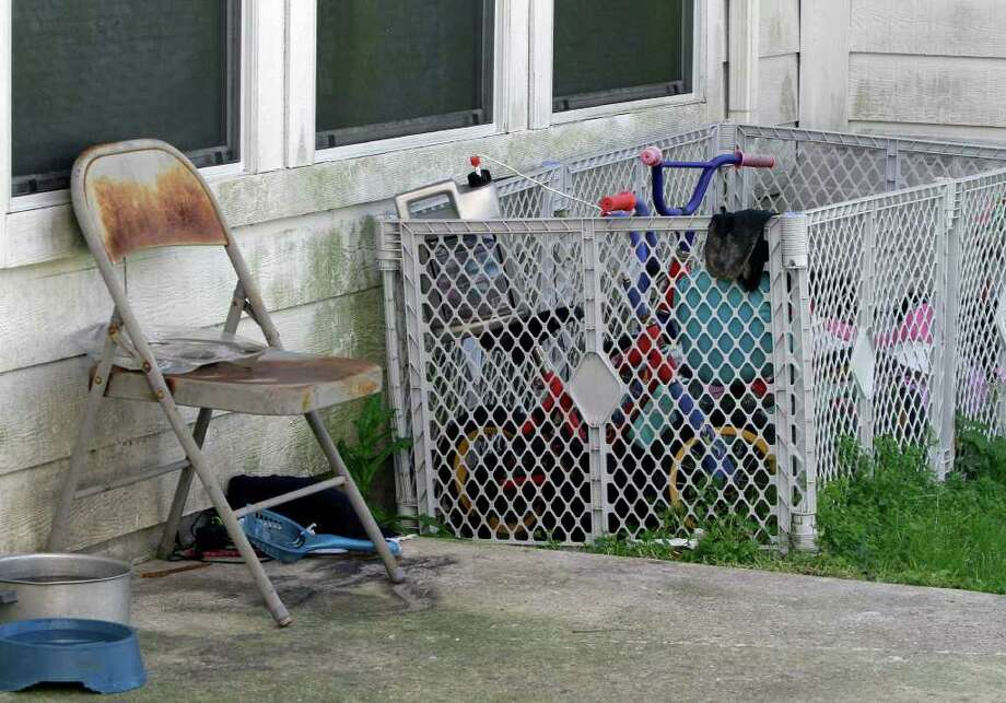 A rusty chair and some toys sit outside a Dayton house where 11 children, some of them reportedly found in restraints,  where removed by children's protective services last month. Photo: Associated Press