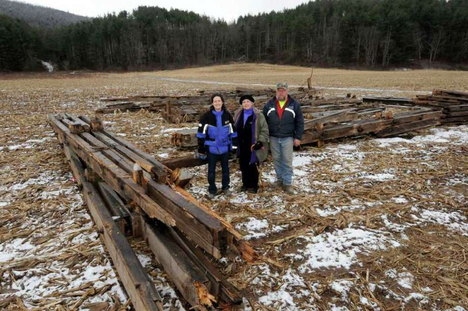 Anne Mattice-Strauch,left, Gail Shaffer,center, and Blenheim DPW supervisor Gerald Felter stand amid pieces rescued of the historic Blenheim covered bridge in Blenheim, N.Y. Friday Feb.24, 2012. ( Michael P. Farrell/Times Union) Photo: Michael P. Farrell