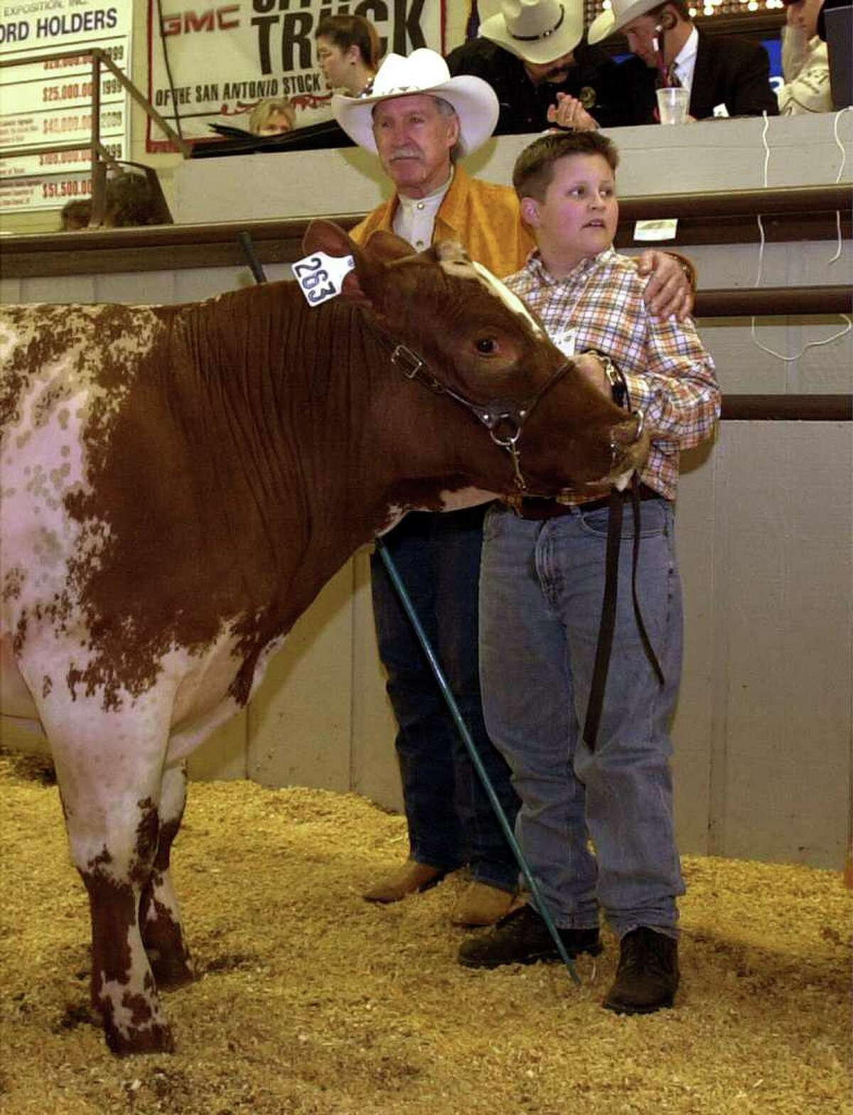 Richard Wallrath (center) stands with 10-year-old Stetson Copus and his grand champion steer, Super Fly, after Wallrath made the highest bid for the steer at $87,500 at the junior live stock auction on Saturday, February 17, 2001.