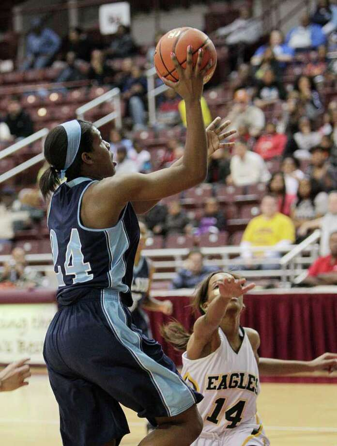 Elsik's Crystal Porter #23 drives to the basket over Cy Falls' Shernise Robertson #14 during the Region III 5A girls basketball finals between Cy Falls and Alief Elsik at the M.O. Campbell Center Feb.  25, 2012 in Houston, Tx. Photo: Bob Levey, Houston Chronicle / ©2012 Bob Levey