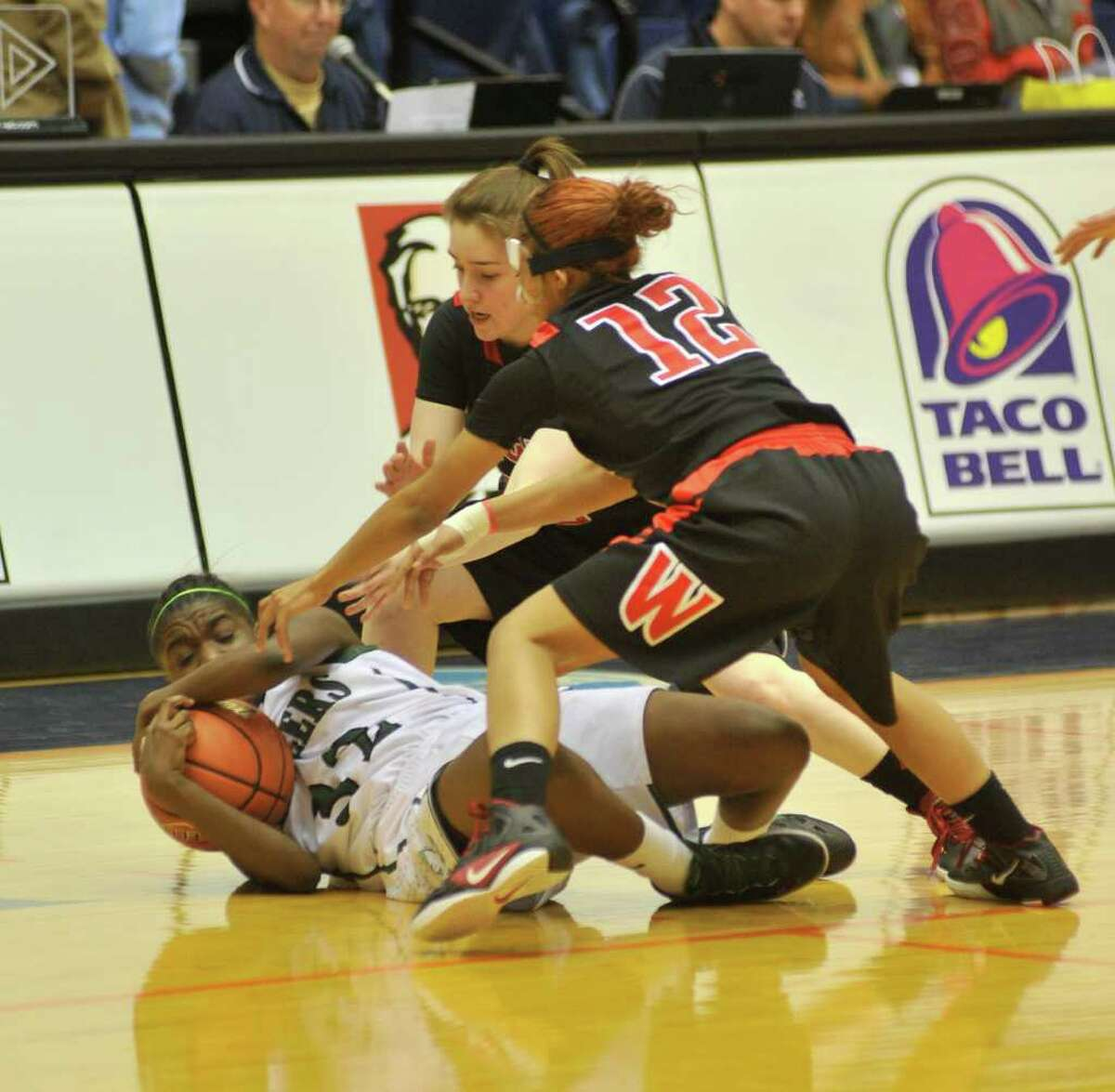 Reagan's Moriah Mack controls a loose ball as Wagner's Corrina Moncada and Aundrea Davis try to steal it during the Region IV-5A championship on Saturday, Feb. 25, 2012, at UTSA's Convocation Center.