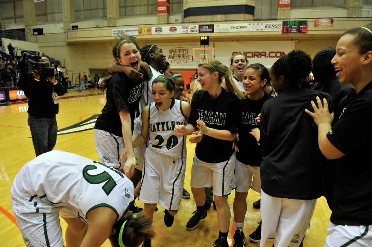 Sabrina Berry (15), Tessa Ramirez (20) and the Reagan Rattlers celebrate the Region IV-5A title Saturday after beating Wagner.