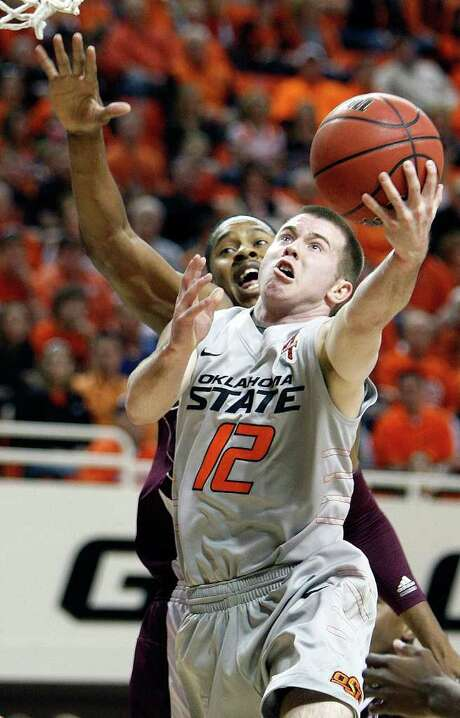 Oklahoma State's Keiton Page (12) takes a shot in front of Texas A&M's Keith Davis in the first half of an NCAA college basketball game in Stillwater, Okla., Saturday, Feb. 25, 2012. Oklahoma State won, 60-42. (AP Photo/The Oklahoman, Nate Billings) TABLOIDS OUT Photo: AP