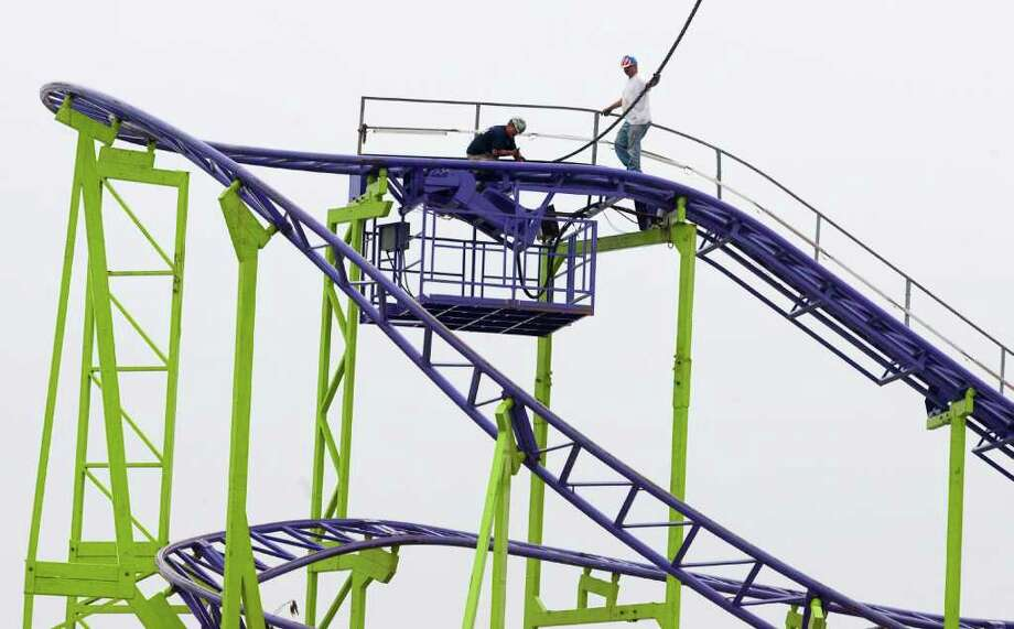 James Murray, left, and Robert Hall work on installing the Dstorm roller coaster at the carnival for RodeoHouston at Reliant Park. This ride is not the same as the one from which a rider plunged to his death last year. Photo: J. Patric Schneider / Houston Chronicle