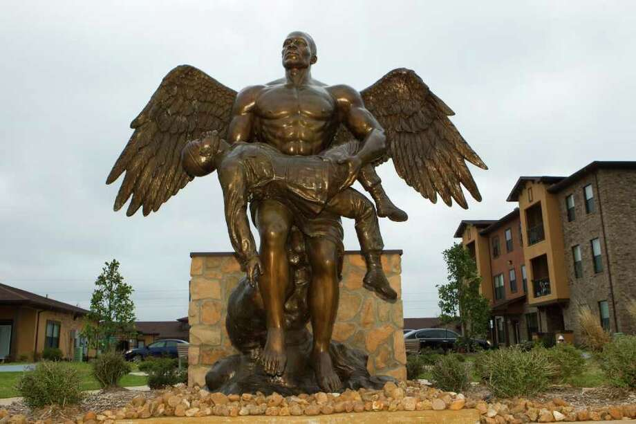 A statue of an angel holding a fallen soldier is the centerpiece of Purple Heart Plaza at the Sierra Meadows Apartments, an affordable residential complex built by the Harris County Housing Authority in Houston. Photo: Brett Coomer / © 2012 Houston Chronicle