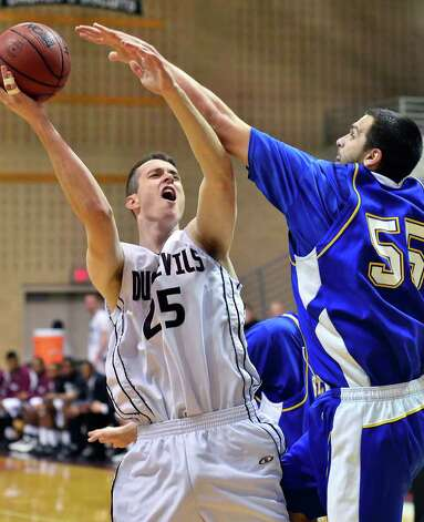 TAMIU's Evan Matteson (25) shoots over the outstreched arm of St. Mary's defender Kevin Kotzur (55) as he goes for a basket Saturday afternoon during the first half of their Heartland Conference game at TAMIU. Photo: CUATE SANTOS / LAREDO MORNING TIMES