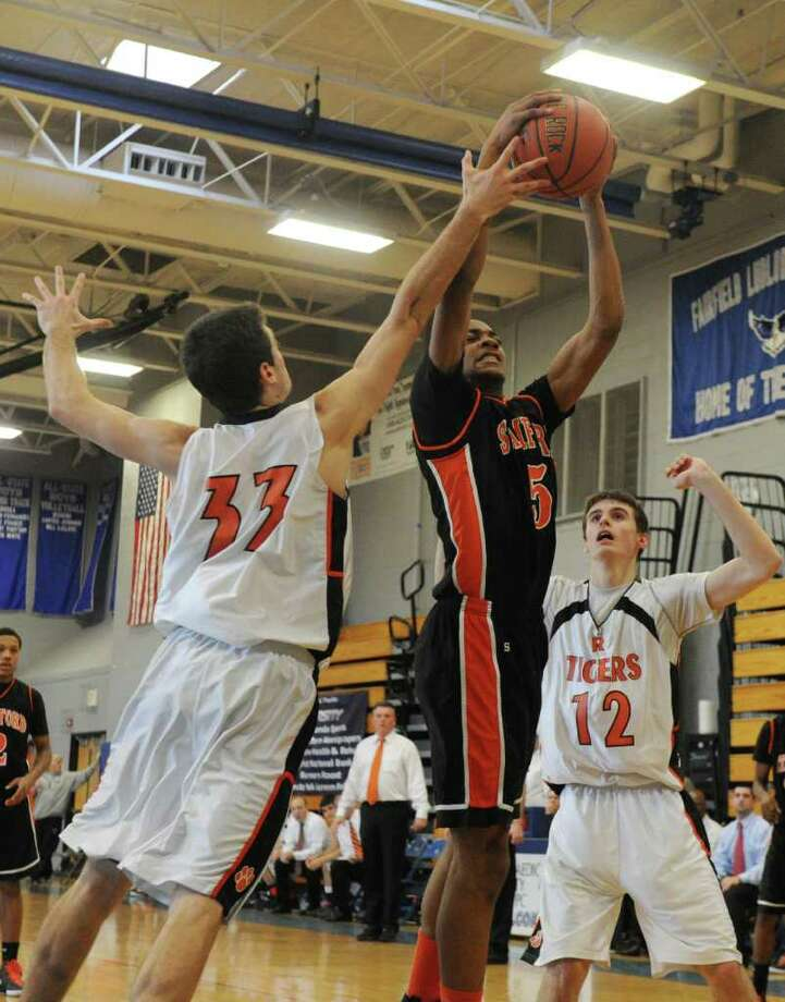 Stamford's Shawn Padilla goes up for a shot as Ridgefield's Jack Heller blocks him as Stamford High School and Ridgefield High face off in the FCIAC boys basketball semifinals at Ludlowe High School in Fairfield, Conn., February 25, 2012. Ridgefield won the game 50-46. Photo: Keelin Daly / Keelin Daly