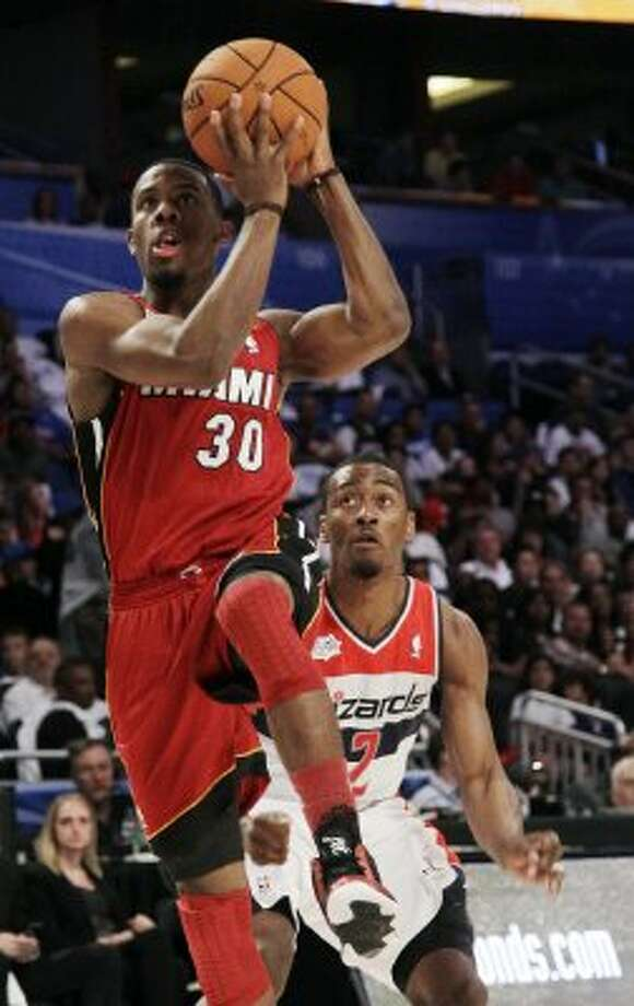 Miami Heat's Norris Cole (30), of Team Shaq, goes for a layup past Washington Wizards' John Wall (2), of Team Chuck, during the NBA All-Star Rising Stars Challenge basketball game in Orlando, Fla. Friday, Feb. 24, 2012. (AP Photo/Chris O'Meara) (AP)