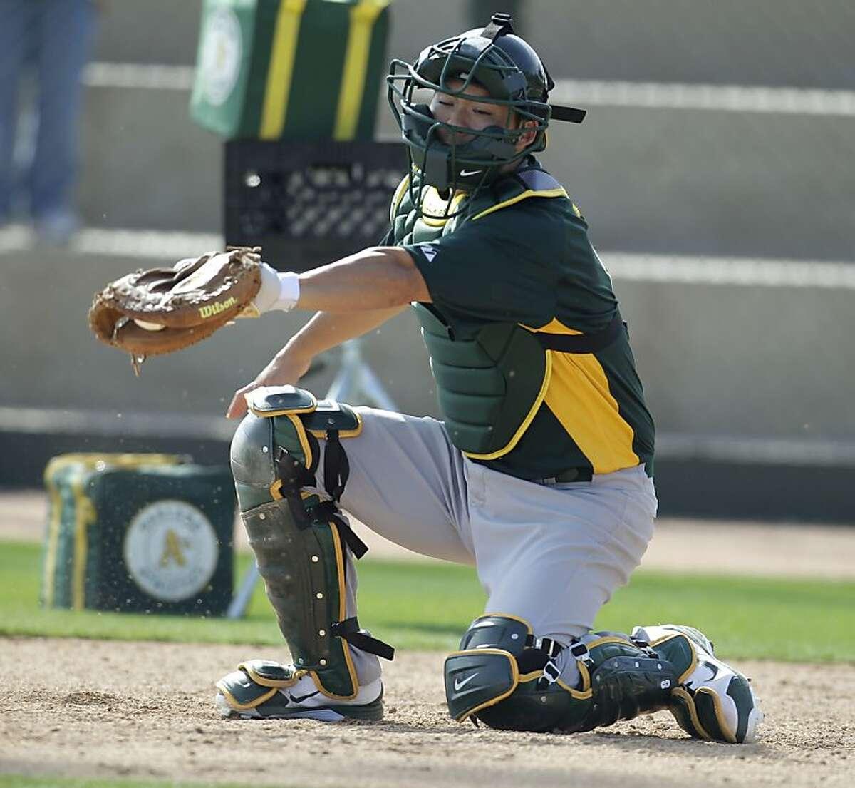 Oakland Athletics' Kurt Suzuki makes a catch during a spring training baseball workout, Monday, Feb. 20, 2012, in Phoenix. (AP Photo/Darron Cummings)