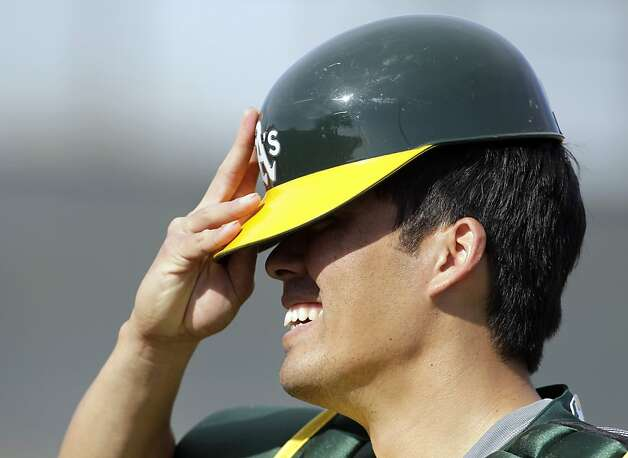 Oakland Athletics' Kurt Suzuki put on his helmet during a baseball spring training workout Monday, Feb. 20, 2012, in Phoenix. (AP Photo/Darron Cummings) Photo: Darron Cummings, Associated Press