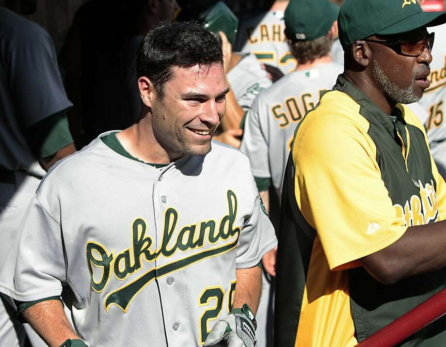 Oakland Athletics' Scott Sizemore, left, smiles as he walks through the dugout after hitting a pinch-hit grand slam off Texas Rangers' Yoshinori Tateyama in the sixth inning of a baseball game Saturday, Sept. 10, 2011, in Arlington, Texas. The shot helpedthe Athletics to an 8-7 win. Athletics hitting coach Gerald Perry is at right. Photo: Tony Gutierrez, AP