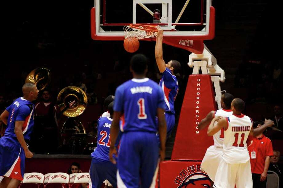 SMU center, Cannen Cunningham, 15, slam dunks the ball during the second half of an NCAA men's basketball game between the University of Houston Cougars and the Southern Methodist University Mustangs, Saturday, February 25, 2012, at Hofheinz Pavilion in Houston, Texas. Houston won 62-59. Photo: TODD SPOTH, For The Chronicle / © TODD SPOTH, 2012