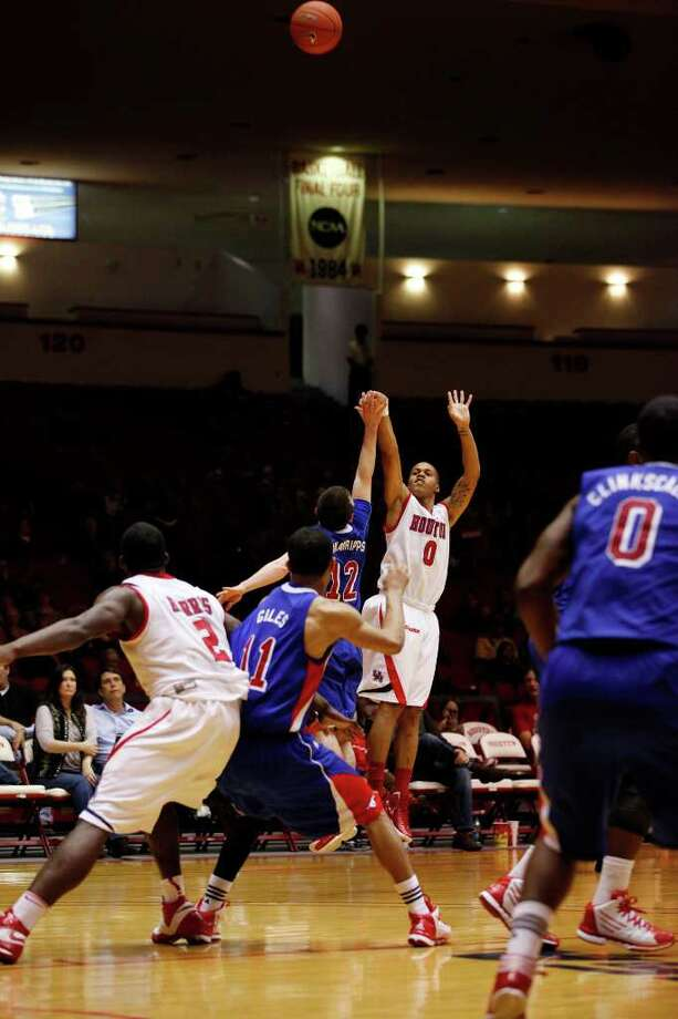 Houston guard Joseph Young, 0, shoots a three point shot during the second half of an NCAA men's basketball game between the University of Houston Cougars and the Southern Methodist University Mustangs, Saturday, February 25, 2012, at Hofheinz Pavilion in Houston, Texas. Houston won 62-59. Photo: TODD SPOTH, For The Chronicle / © TODD SPOTH, 2012