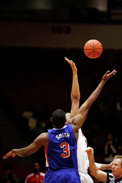 SMU guard, Leslee Smith, 3, wins the opening tipoff during the first half of an NCAA men's basketbal