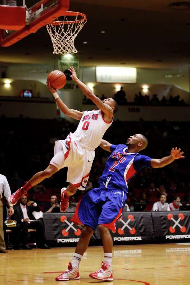 Houston guard Joseph Young, 0, puts up 2 points on a layup and is fouled by SMU forward Shawn Williams, 2, during the first half of an NCAA men's basketball game between the University of Houston Cougars and the Southern Methodist University Mustangs, Saturday, February 25, 2012, at Hofheinz Pavilion in Houston, Texas.  Photo: TODD SPOTH, For The Chronicle / © TODD SPOTH, 2012