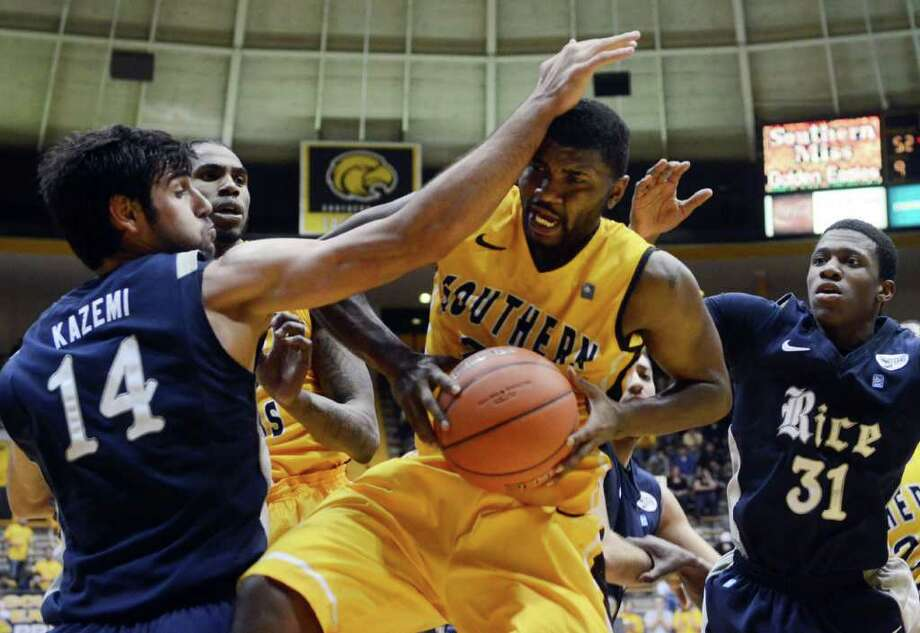 Southern Mississippi's Angelo Johnson (23) makes a rebound as Rice's Arsalan Kazemi (14) attempts to block a shot during NCAA college basketball game  Saturday, Feb. 25, 2012, in Hattiesburg, Miss. (AP Photo/The Hattiesburg American, Bryant Hawkins)  NO SALES Photo: Bryant Hawkins / Bryant Hawkins
