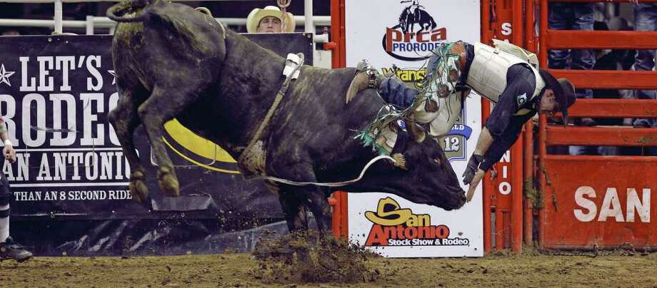 Beau Brooks exits frontwards in the bull riding event at the final rodeo performance at the San Antonio Livestock Show & Rodeo on February 25, 2012. Photo: TOM REEL, San Antonio Express-News / San Antonio Express-News