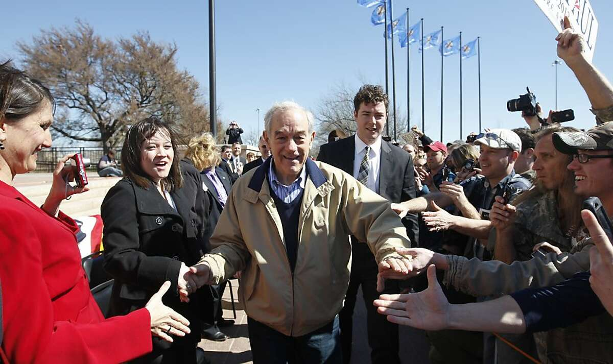 Republican presidential candidate Rep. Ron Paul, R-Texas, shakes hands as he arrives at a rally in Oklahoma City, Saturday, Feb. 25, 2012. (AP Photo/Sue Ogrocki)