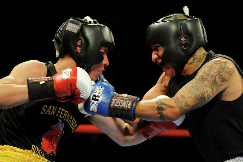 Gabriel Delgado (right) and David Murillo (left) throw punches during the novice 141-pound lightweight bout at the San Antonio Regional Golden Gloves Championship at the Scottish Rite Cathedral on Saturday, Feb. 25, 2012. Photo: John Albright, For The Express-News