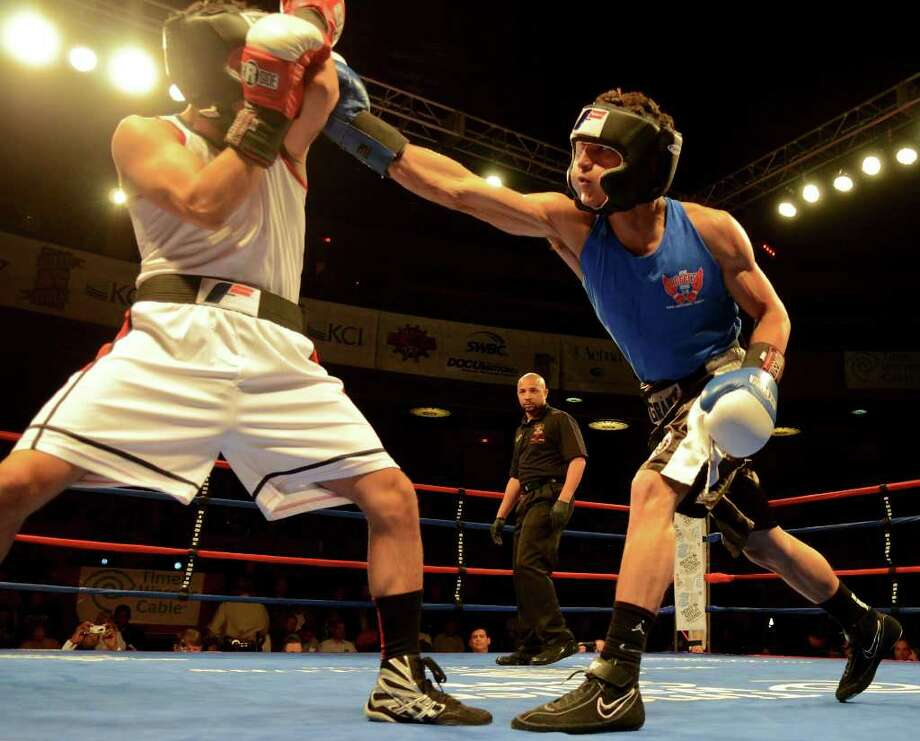 Mark Martinez (right) lands a punch against Carlos Vergara (left) during the open 141-pound lightweight bout at the San Antonio Regional Golden Gloves Championship at the Scottish Rite Cathedral on Saturday, Feb. 25, 2012. Photo: John Albright, For The Express-News