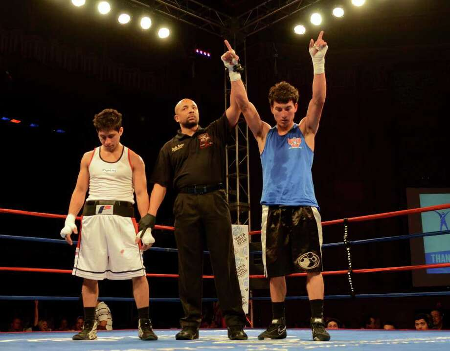 Mark Martinez (right) is announced the winner over Carlos Vergara (left) in the open 141-pound lightweight bout at the San Antonio Regional Golden Gloves Championship at the Scottish Rite Cathedral on Saturday, Feb. 25, 2012. Photo: John Albright, For The Express-News