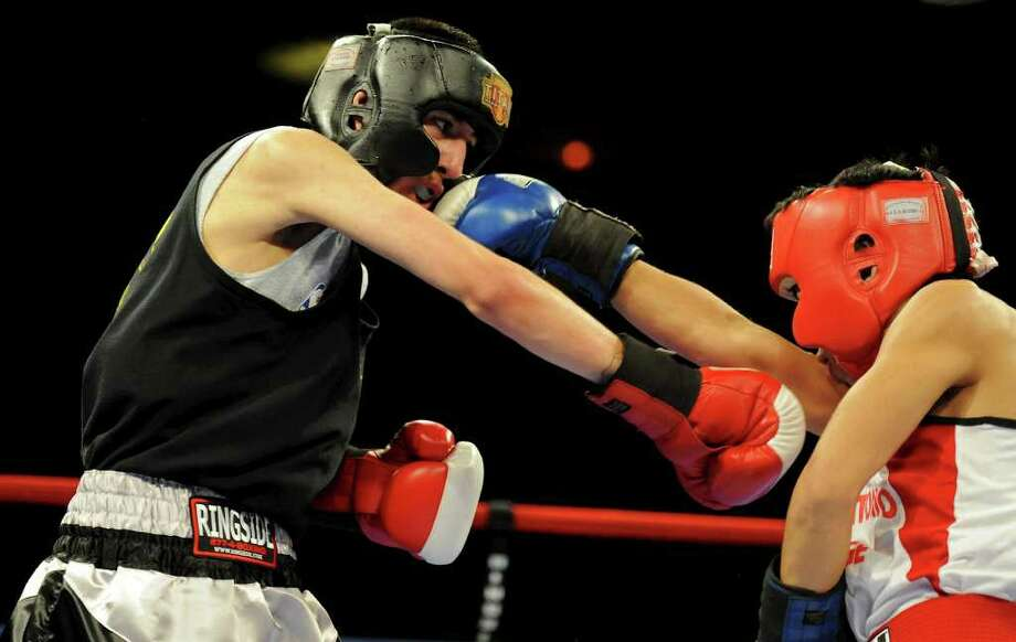 Jade Flores (left) and Dale DelRosario (right) throw punches during the novice 112-pound fly bout at the San Antonio Regional Golden Gloves Championship at the Scottish Rite Cathedral on Saturday, Feb. 25, 2012. Photo: John Albright, For The Express-News