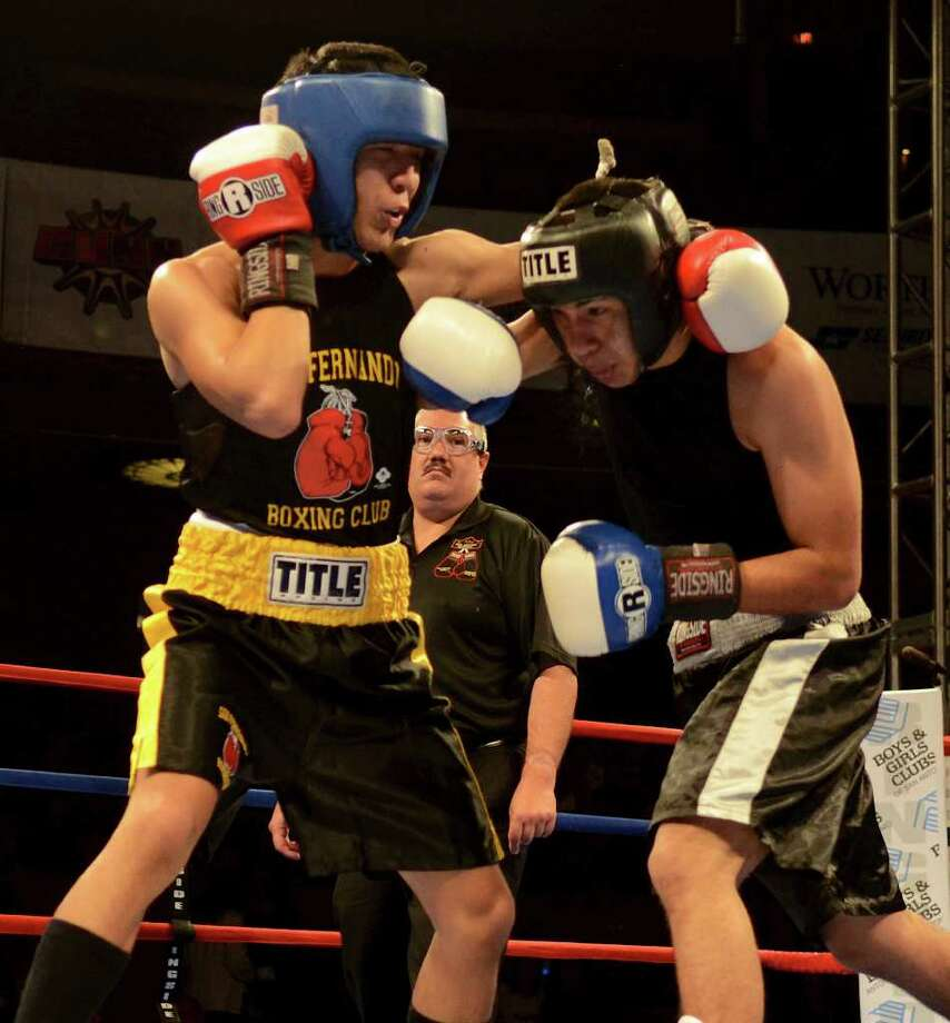 Kendo Castaneda (left) and Christian Santibanes (right) throw punches during the open 132-pound lightweight bout at the San Antonio Regional Golden Gloves Championship at the Scottish Rite Cathedral on Saturday, Feb. 25, 2012. Photo: John Albright, For The Express-News