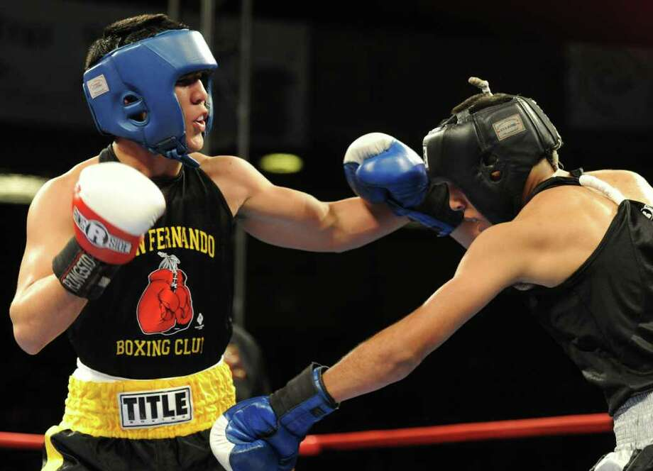 Kendo Castaneda (left) tries to land a punch to the head of Christian Santibanes (right) during  the open 132-pound lightweight bout at the San Antonio Regional Golden Gloves Championship at the Scottish Rite Cathedral on Saturday, Feb. 25, 2012. Photo: John Albright, For The Express-News