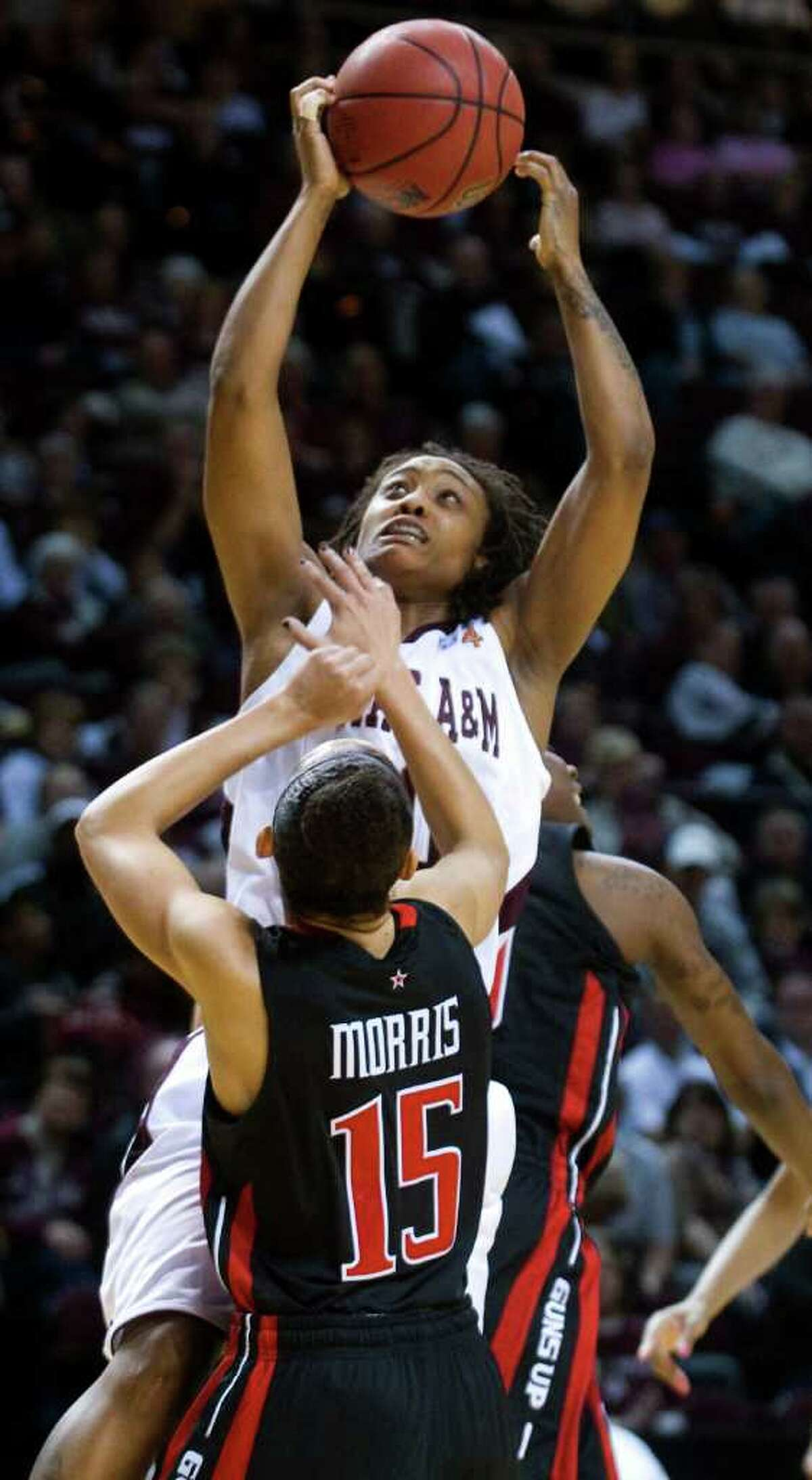 Texas A&M's Tyra White grabs the offensive rebound over Texas Tech's Casey Morris during the first half of an NCAA college basketball game, Saturday, Feb. 25, 2012, in College Station.