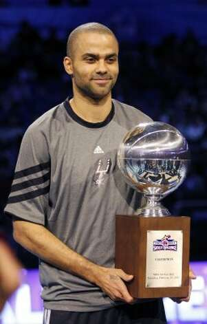 San Antonio Spurs' Tony Parker (9) holds the NBA All-Star Skills Challenge basketball competition trophy after winning the event in Orlando, Fla., Saturday, Feb. 25, 2012. (AP Photo/Lynne Sladky) (AP) / SA