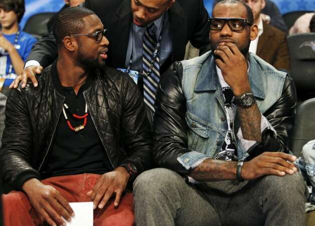 Miami Heat's Dwyane Wade, left, and Lebron James sit courtside during the NBA All-Star festivities in Orlando, Fla., Saturday, Feb. 25, 2012. (AP Photo/Lynne Sladky) (AP) / SA